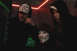 three hackers around a computer wearing anonymous / guy fawkes masks